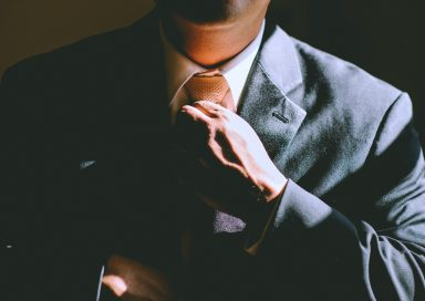 A person adjusts their tie as they get ready to go to work