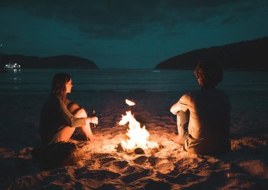 Two people sit on a beach next to a fire, enjoying their moment together
