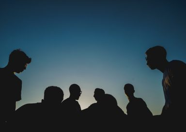 Silhouettes of a group of people against a dawn sky