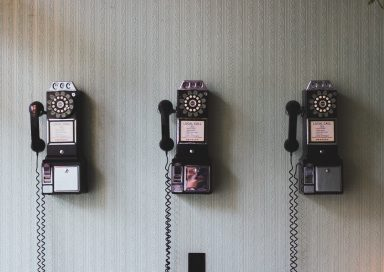 3 retro telephones fixed to a wall waiting to be answered