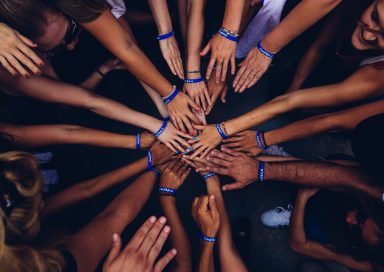 A group of people put their hands into a circle, showing togetherness